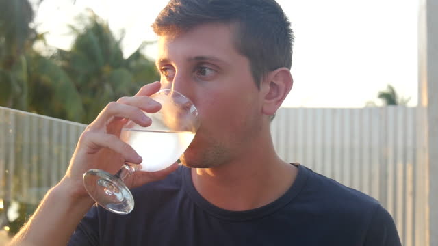 Young man enjoys glass of ice cold water, in tropics
