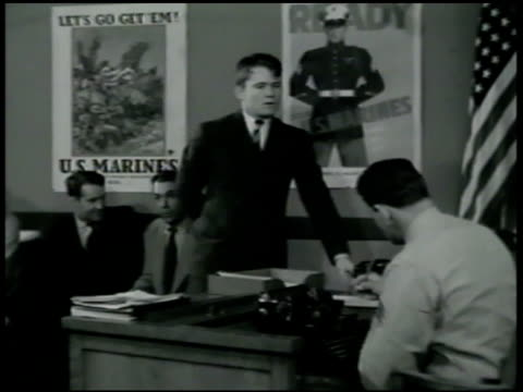 young man enlisting in office. vs man talking to officer at desk '... i want to fight.' 'what's your name?' 'charlie bulas.' marine corps id card... - 1942年点の映像素材/bロール