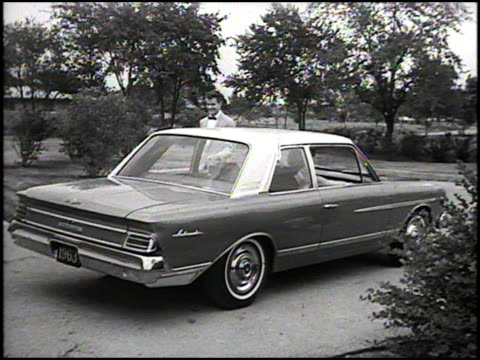 vidéos et rushes de young man escorts his date to the passenger side of his 1963 amc ambassador; helps her into the car, closes her door, and then gets behind the wheel;... - cadrage aux genoux