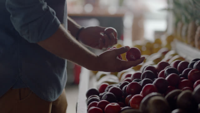 young man examines and collects plums to buy at a farmers market - only men stock videos & royalty-free footage