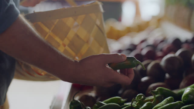 cu. young man examines jalapeno peppers at a farmers market - picking up stock videos & royalty-free footage