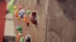 young man exercising at indoor climbing gym wall