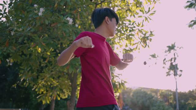 vídeos y material grabado en eventos de stock de joven haciendo ejercicio para estar sano en el parque - camiseta