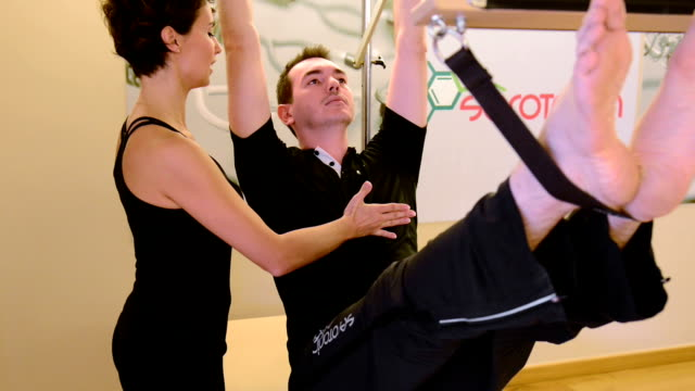 young man exercising in the pilates studio - pilates stock videos and b-roll footage