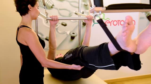 vídeos y material grabado en eventos de stock de hombre joven en el ejercicio de pilates estudio - pilates