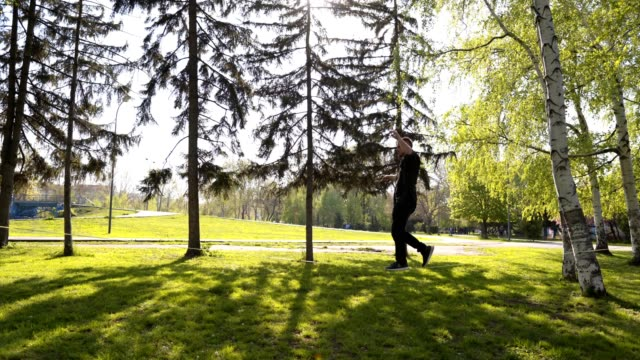 young man exercising on a tightrope at a park - tightrope walking stock videos & royalty-free footage