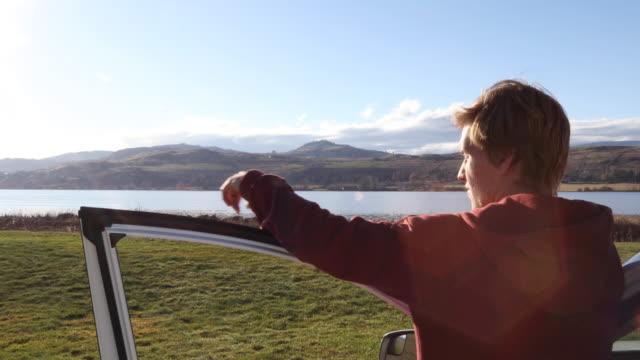 young man exits car door - car door stock videos & royalty-free footage