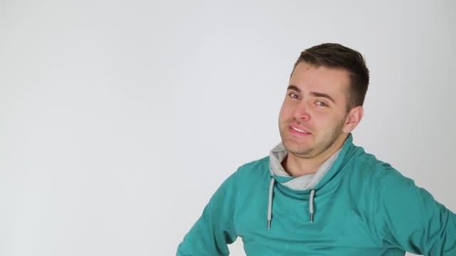 vidéos et rushes de expressions faciales de jeune homme, projectile de studio, fond blanc - indécision