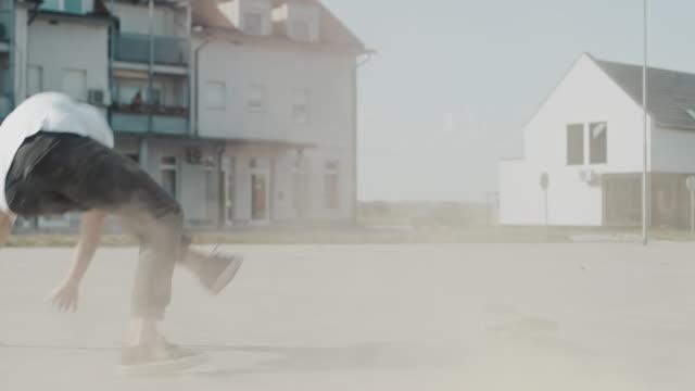 ms young man cade da skateboard in soleggiata piazza della città - falling video stock e b–roll