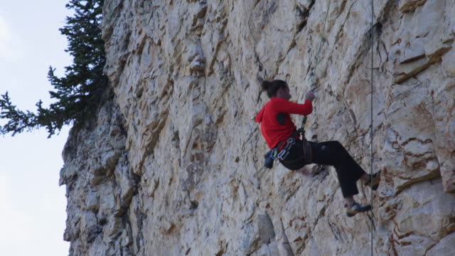 A young man falls while rock climbing.