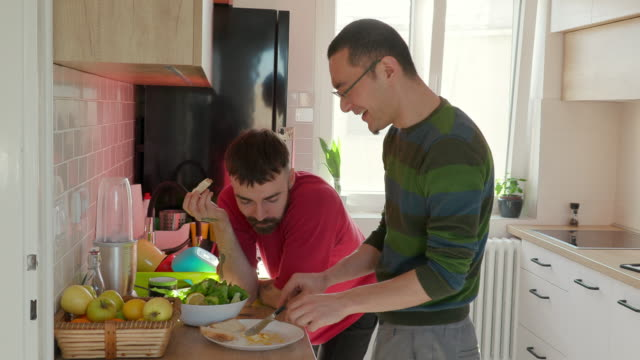 young man feeding his boyfriend with fried eggs for fun - pianale da cucina video stock e b–roll
