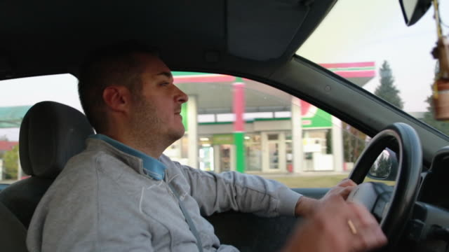 young man feeling tired inside of car. exhausted man yawning and covering mouth with hand while driving a car - yawning stock videos & royalty-free footage