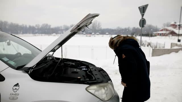 vidéos et rushes de jeune homme remplissant le liquide de lave-glace - capot de voiture