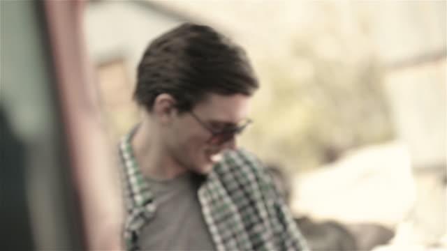vídeos de stock e filmes b-roll de young man fills up classic convertible at desert gas pump - posto de gasolina