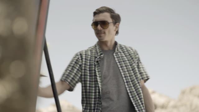 young man fills up convertible at old-fashioned gas pump - fare il pieno di benzina video stock e b–roll