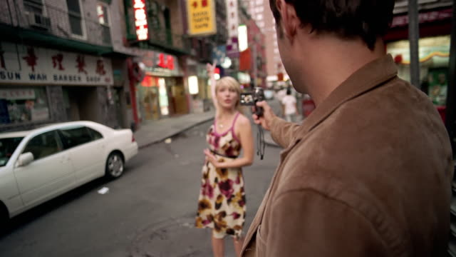 slo mo, selective focus, young man filming woman with digital camera in chinatown, new york city, new york, usa - digital camera stock videos and b-roll footage
