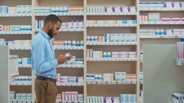 ds young man finding the right bottle on the stacked shelf in the pharmacy - pharmacy stock videos and b-roll footage