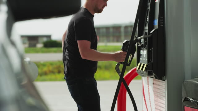 Young man finishes pumping gas, removes and hangs up the nozzle, closes the gas cap, opens the car door and sits in the driver's seat.