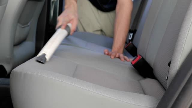 vidéos et rushes de jeune homme finition vacuuming siège de voiture et montrant des pouces vers le haut - satisfaction
