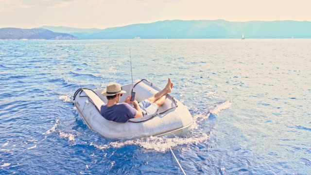 4k young man fishing and using smart phone in raft being pulled on sunny summer ocean, real time - remote location phone stock videos & royalty-free footage