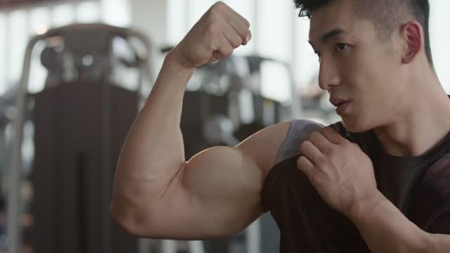 vidéos et rushes de young man flexing muscles at gym,4k - montrer