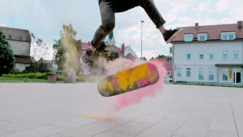 ms super slow motion young man flipping skateboard with powder in town square - super slow motion stock videos & royalty-free footage