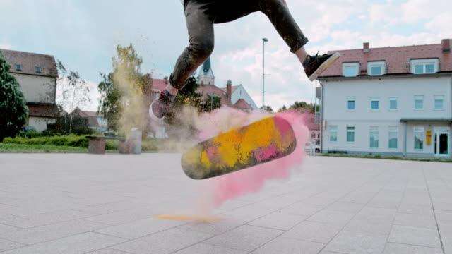 vídeos de stock, filmes e b-roll de ms super slow motion jovem capotando skate com pó na praça da cidade - velocidade alta