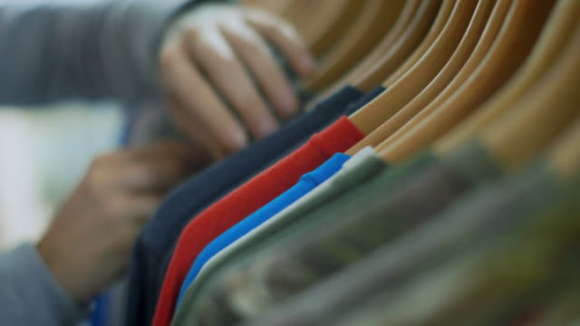 young man flips through rack and picks out shirt in modern clothing store - rack stock videos & royalty-free footage