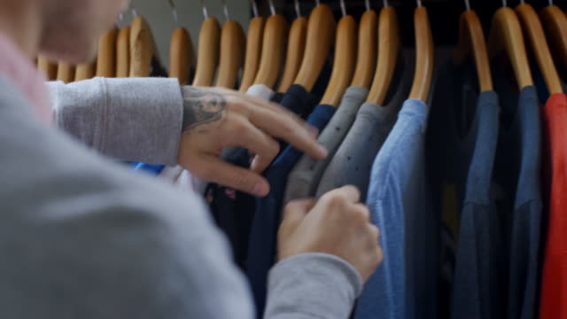 young man flips through sale rack and picks out t-shirt in clothing store - maglietta video stock e b–roll