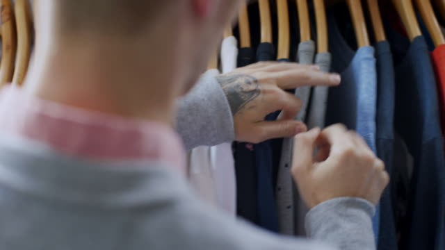 Young man flips through t-shirts in clothing store, picks one to look at and returns it to rack