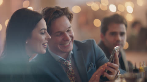 stockvideo's en b-roll-footage met young man flirts with a beautiful woman sitting at the bar, look at his phone together - klanten georiënteerd