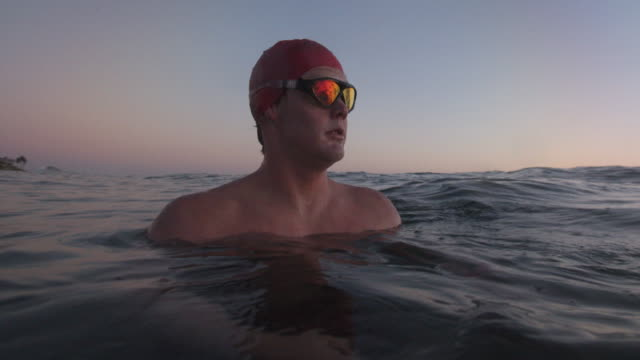 sm cu young man floating in the sea at dusk - triatleta video stock e b–roll