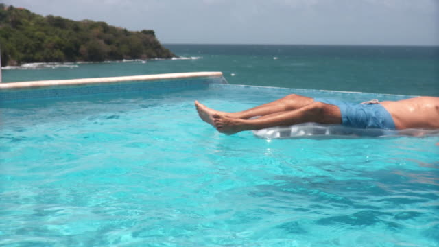 MS Young man floating past on inflatable raft in infinity pool, with ocean in background/ Scarborough, Tobago, Trinidad and Tobago