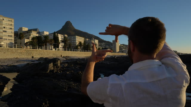 Young man framing Cape Town at sunset