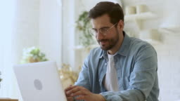 Young man freelancer using laptop studying working online at home