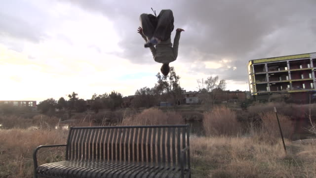 A young man freerunner doing parkour and a flip off a park bench.