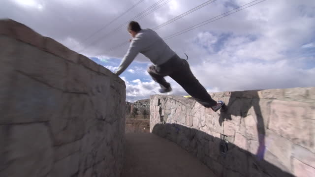 A young man freerunner doing parkour and running on stone wall.