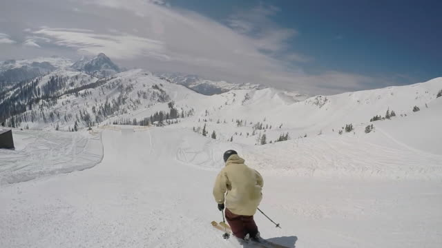 A young man freestyle skier skiing in a terrain park on a snow covered mountain. - Slow Motion