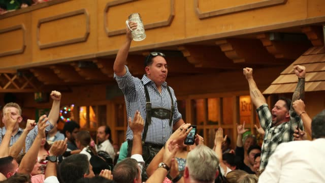 A young man from the USA on his bachelor party holds up his empty glass after downing its beer in the Armbrustschuetzenzelt tent on the opening day...