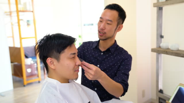 Young man get his hair cut and styled at a hair salon
