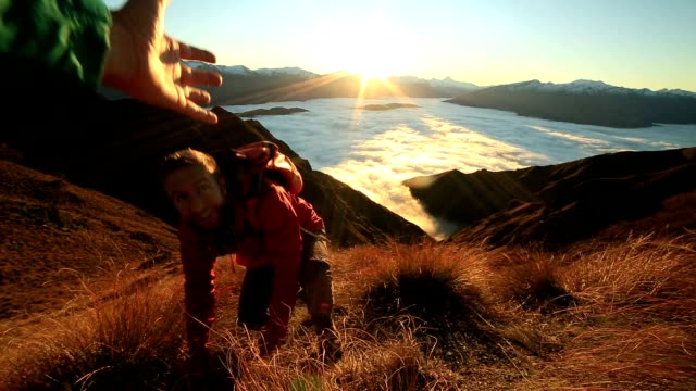 young man gets assistance at mountain top - help single word stock videos and b-roll footage