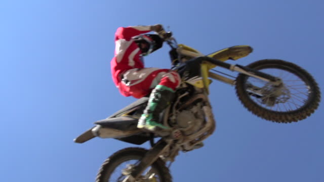 A young man getting air while riding a motocross dirt motorcycle off a jump. - Slow Motion