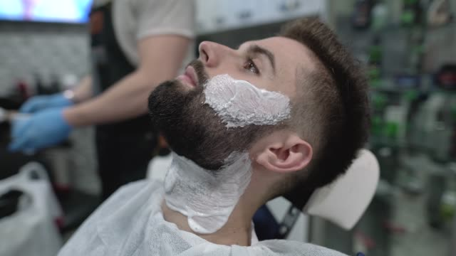 young man getting beard treatment at the barbershop - beard stock videos & royalty-free footage
