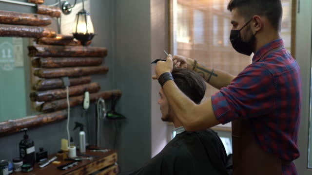 young man getting haircut at the barber shop - tattoo stock videos & royalty-free footage