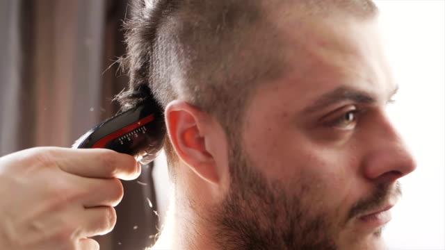 vídeos de stock, filmes e b-roll de jovem, ficando o cabelo aparado por máquina de corte de cabelo em câmera lenta - evento anual
