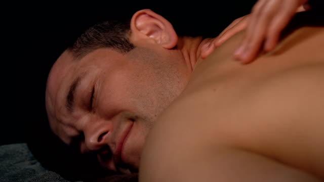 stockvideo's en b-roll-footage met jonge man krijgt massage in spa - masseren