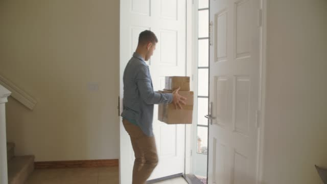ws young man getting packages delivered at home - door stock videos & royalty-free footage