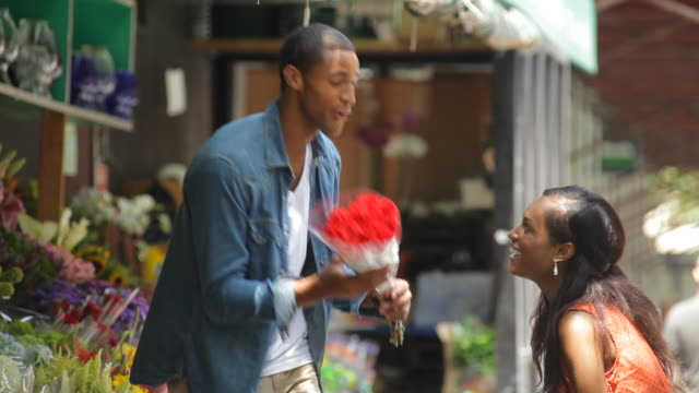 a young man gives a bouquet of flowers from a street stand to his girlfriend. - bouquet stock videos & royalty-free footage
