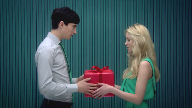 Young man gives a present to girlfriend and they kiss