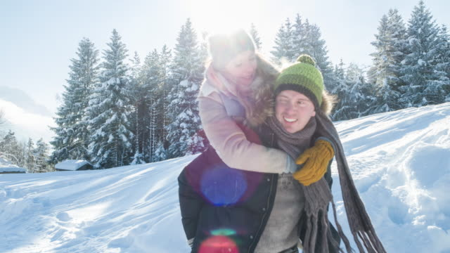 A young man gives his girlfriend a piggy-back ride in winter landscape